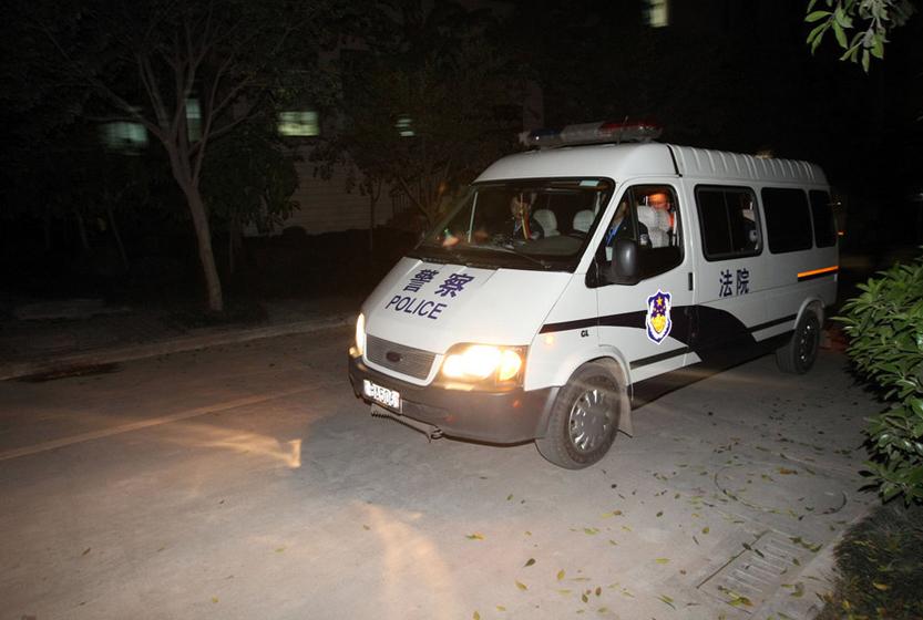 """2011年4月19日,李庄""""漏罪""""案在重庆市江北区法院开庭审理。图为运送李庄的警车。 渝友/CFP _李庄""""漏罪""""案在重庆公开庭审"""