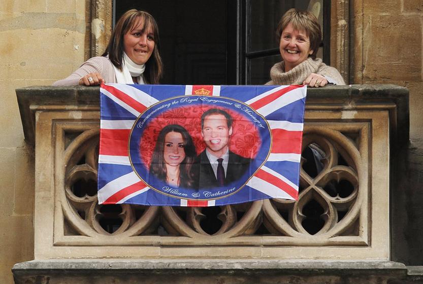 2011年4月29日,英国伦敦,民众静待大婚开始。王室婚礼准备工作进入最后阶段。图为两位伦敦市民在阳台拉开威廉王子及其未婚妻米德尔顿的旗帜。 Sean Gallup/Getty Images/CFP _英国威廉王子世纪婚礼