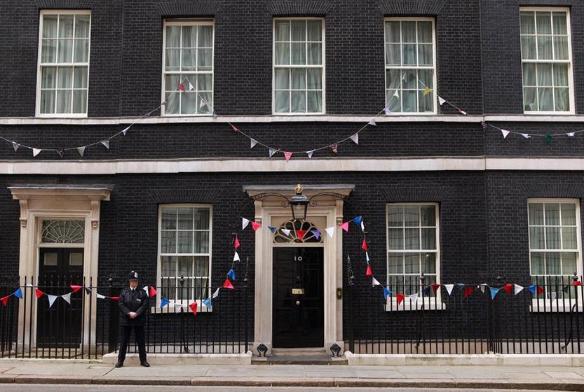 2011年4月28日,英国伦敦,一名警官在为婚礼装饰一新的首相府前。 Oli Scarff/Getty Images/CFP _英国威廉王子世纪婚礼