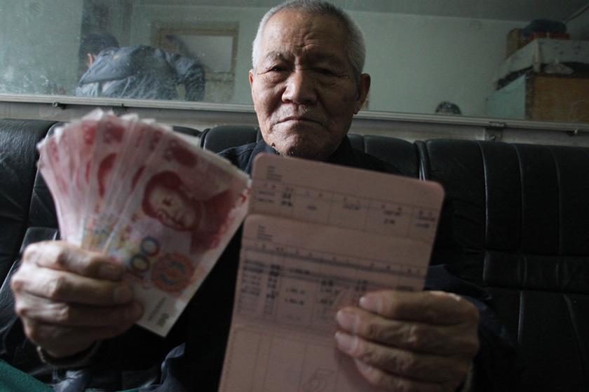 11月6日,石家庄,80岁的任锡禄老人展示从邮储银行取回的11张百元假钞。 CFP_石家庄多位老人领取退休金遭遇假币