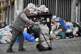 """2011年6月,在希腊大批债务即将到期的关键时刻,穆迪等把希腊主权信用评级降至全球最低水平,即""""垃圾级""""。这是10月14日,一名老人推车经过希腊雅典街头的垃圾堆。"""