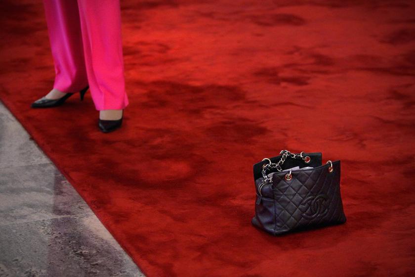 3月10日,北京,全国政协十一届五次会议第三次全体会议举行前,一名女委员接受拍照,地上放着的是她的香奈儿包。  Feng Li/Getty Images/CFP_财新每周图片(2012.3.10-3.16)
