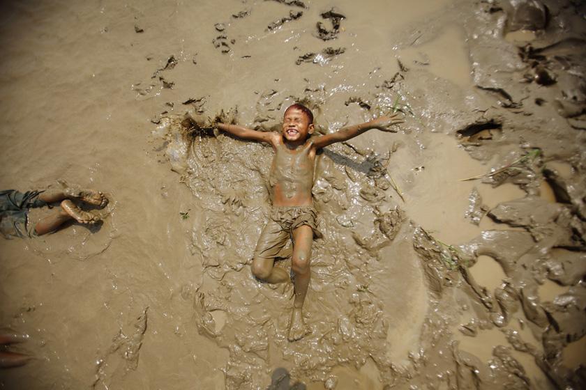 2012年3月20日,缅甸勃固河岸,一个孩子在泥浆中玩耍。 REUTERS/Staff_财新每周图片(2012.3.17-3.23)
