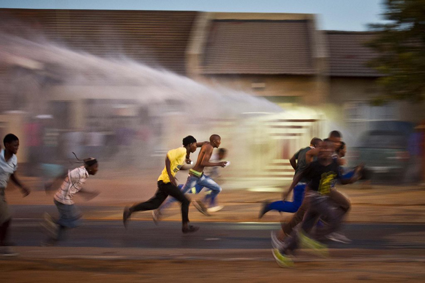 2012年3月19日,南非Ratanda,示威者逃离警察的水枪喷射。抗议电力中断的示威者点燃了市政局办公室旁边的两间房屋,并与警察发生冲突。 Gallo Images/Getty Images/CFP_财新每周图片(2012.3.17-3.23)