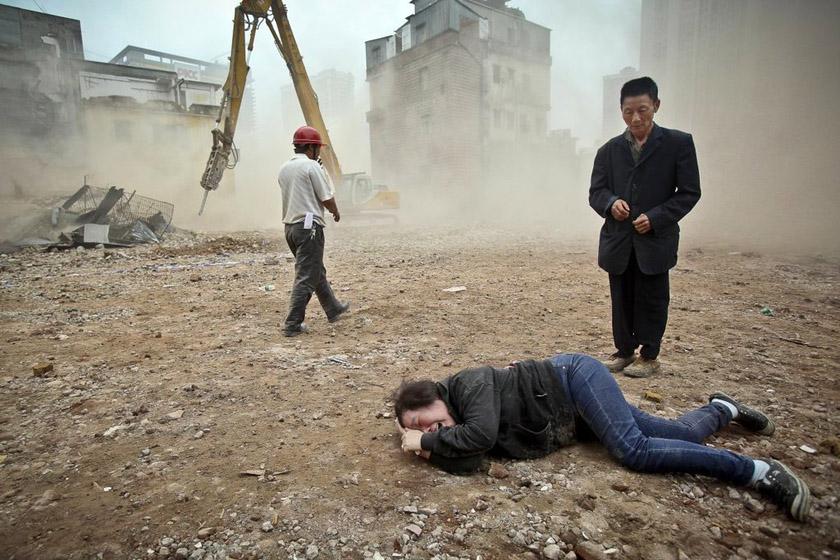 """2012年3月21日,广州杨箕村,在对永巩二横巷8号的李洁娥家进行拆除时,永巩二横7号黄素芳的住楼被""""不慎""""挖倒一半。黄素芳情绪激动,欲冲入灰尘进入自己的住楼,但被施工方拦住,并发生肢体冲突,芳姨倒地痛苦,一位帮她看守房子的外省老乡在旁无助地站着。 东方IC_财新每周图片(2012.3.17-3.23)"""