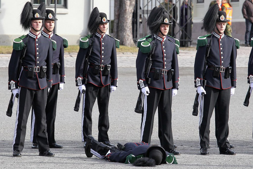 2012年3月20日,挪威奥斯陆,在查尔斯王子夫妇抵达阿克斯胡斯城堡出席一个花环敬献仪式时,一名参加仪式的士兵晕倒,他的同伴依然站着纹丝不动。 Chris Jackson/Getty Images/CFP_财新每周图片(2012.3.17-3.23)