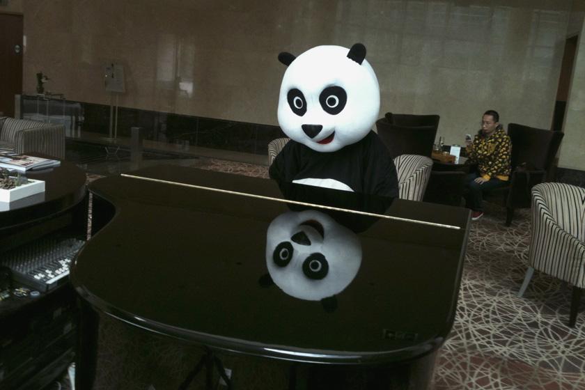 2012年3月18日,北京,在一家酒店的商业活动上,一名扮成熊猫的女子在看一架钢琴。 REUTERS/Jason Lee_财新每周图片(2012.3.17-3.23)
