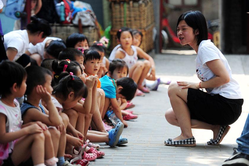 """2010年7月7日,北京西城区四环市场,志愿者正在给外来务工人员的孩子们讲故事。四环游戏小组由北师大学前教育师生创办,为四环市场流动儿童提供学前教育。潘之望/CFP_民政部长谈""""结社"""""""