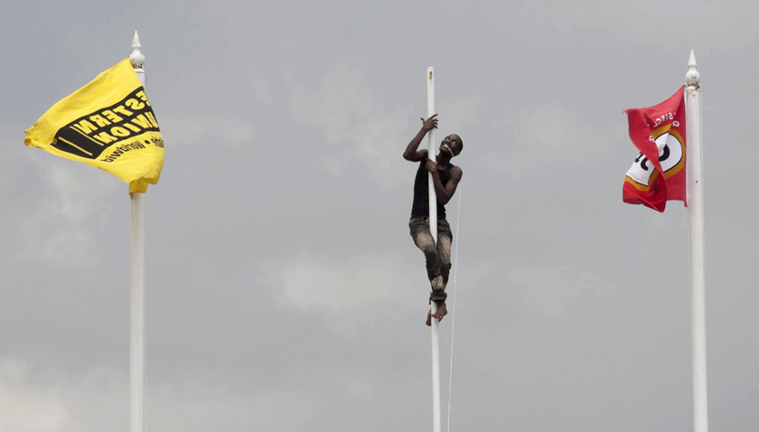 2012年3月27日,牙买加金斯敦,一名工作人员在国家体育馆爬上旗杆准备悬挂旗帜,为中学生田径运动会做准备。 REUTERS/Gilbert Bellamy_财新每周图片(2012.3.24-3.30)