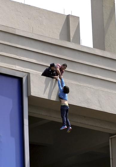 2012年3月26日,浙江义乌国际商贸城五区97号门附近有女孩在五楼顶屋檐边躺卧着情绪激动随时有掉下来的可能,随后赶来的救援人员成功将女孩解救。 CFP_财新每周图片(2012.3.24-3.30)