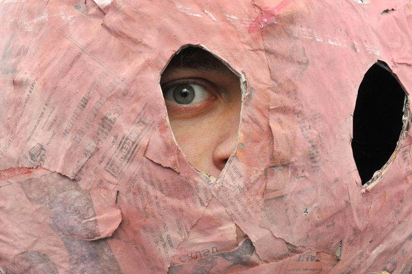 2012年3月24日,俄罗斯圣彼得堡,一名参加示威的反政府抗议者从面罩中向外看。 OLGA MALTSEVA/东方IC_财新每周图片(2012.3.24-3.30)