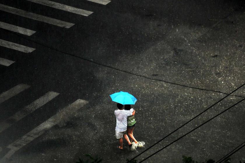 7月10日傍晚,北京突降暴雨,两名行人互相搀扶淌着水在雨中前行。 王苡萱/CFP_北京暴雨致多处积水