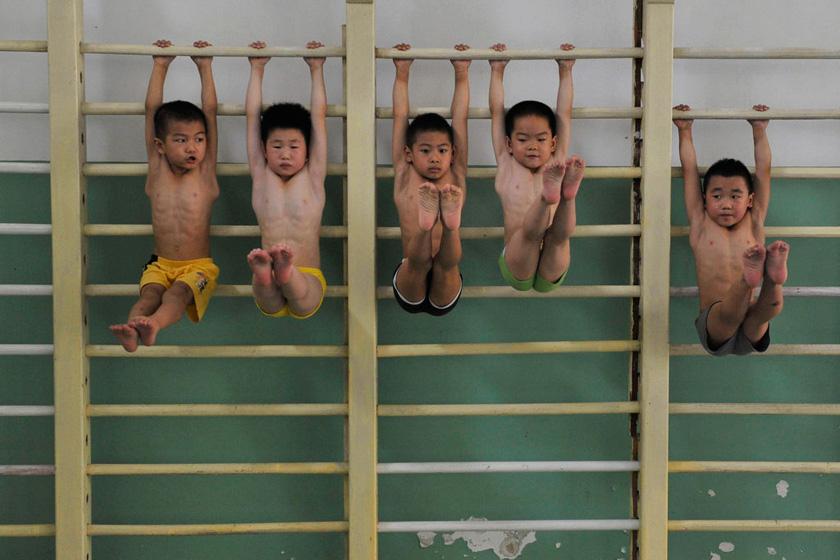 7月6日,南京中山路体校体操房内,小队员们在趴架上吊臂提腿,训练形体。  安心/CFP_财新每周图片(2012.7.7-7.13)