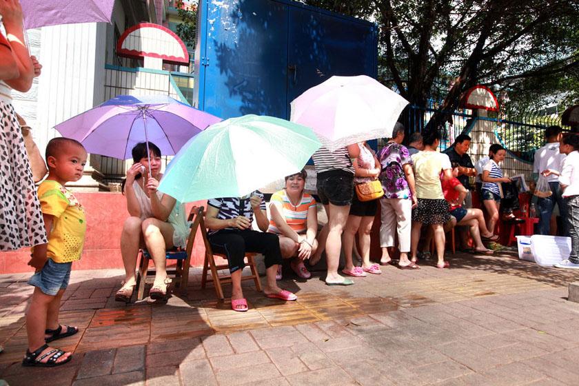 """7月11日上午,广西柳州,距报名还2天时间,家长已经开始在烈日下排队。 颜篁/CFP_柳州一幼儿园招生引发""""排队大战"""""""