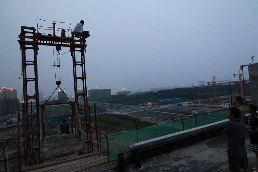 8月21日,郑州,60多岁的农民工龙师傅和李师傅爬上近20米高的铁架讨薪,后被工友搀扶下。  CFP_两位60多岁农民工爬铁架讨薪