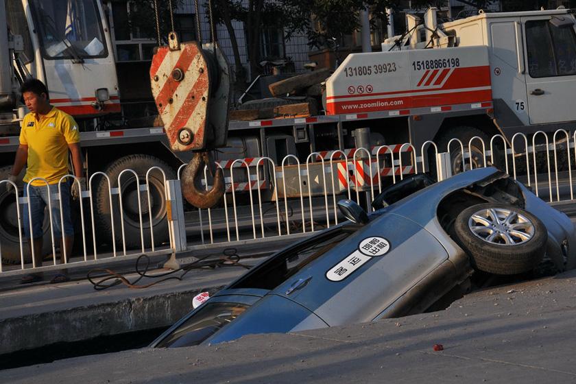 8月29日,陷入坑内的轿车。   胡晓华/东方IC_河北邯郸道路塌陷 出租车陷入大坑