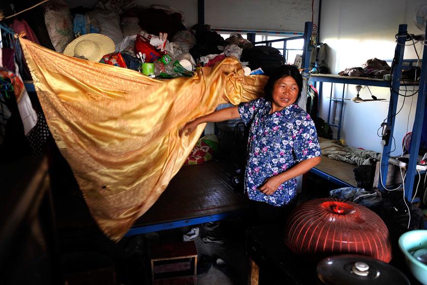 """8月22日,郑州,四川遂宁县54岁的苟素英撩起这道门帘说,""""这就是我们的夫妻房。""""  华商报胡国庆/CFP_农民工夫妻生活现实"""