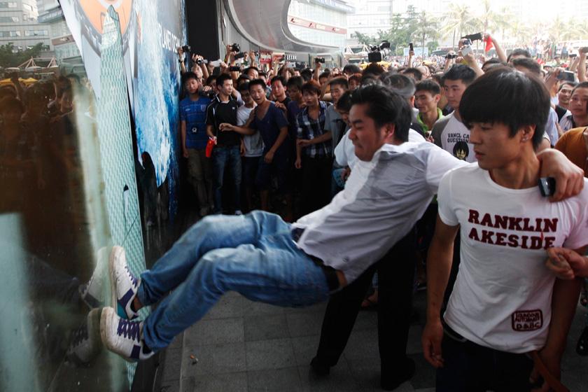 9月16日,深圳,几位抗议者用腿踹一家日资百货公司的大门。 Siu Chiu/REUTERS_多地反日游行现暴力