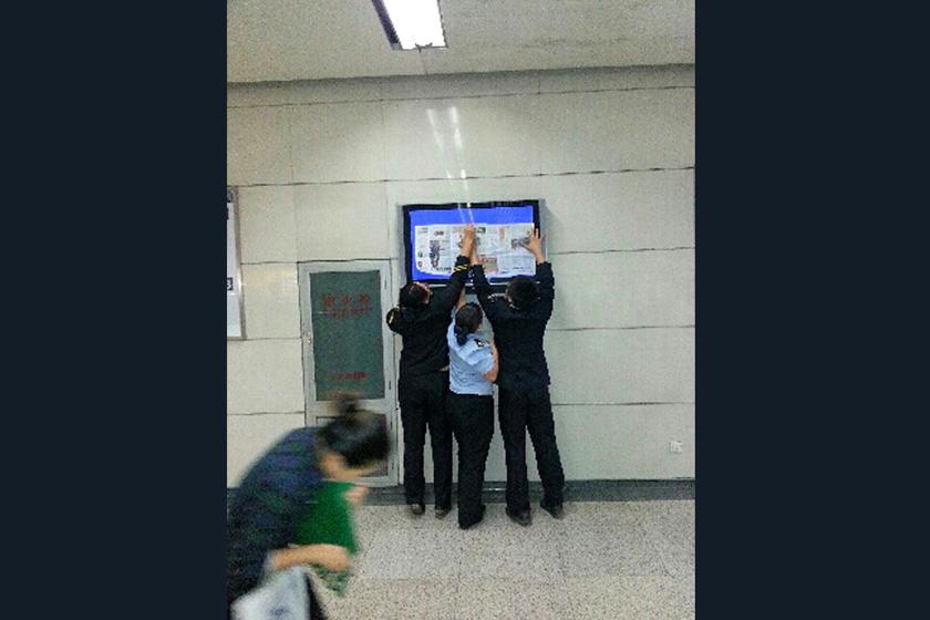 """信息显示屏出现""""王鹏你妹""""四个字, 地铁工作人员正忙着往屏幕上糊报纸"""