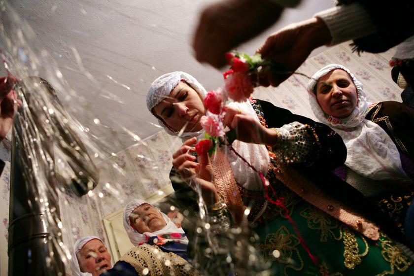 2008年1月6日,保加利亚Ribnovo村,妇女正在为新娘Letfe Mekerozova准备面纱。  BORYANA KATSAROVA/东方IC _保加利亚奇特婚俗 新娘涂白漆冬季出嫁