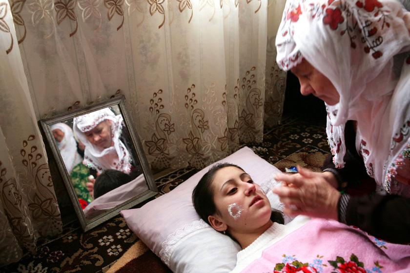 2008年1月6日,保加利亚Ribnovo村,几名妇女正在为新娘Letfe Mekerozova化妆。   BORYANA KATSAROVA/东方IC _保加利亚奇特婚俗 新娘涂白漆冬季出嫁