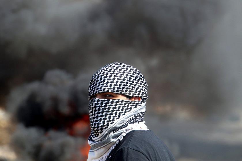 当地时间2012年10月19日,约旦河西岸,一名巴勒斯坦示威者看着以色列士兵与抗议者之间发生冲突。   JAAFAR ASHTIYEH/东方IC_财新每周图片(2012.10.20-10.26)
