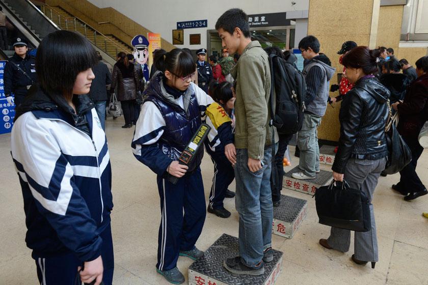 11月08日,太原火车站进站口,身穿校服的安检员正在对入站旅客进行安全检查。    CFP_太原保卫十八大 学生安检员上岗执勤