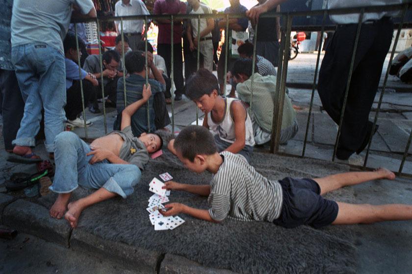 2000年5月23日,广东深圳,几个流浪孩子在街头打牌消磨时间。他们每天在同样的时间同样的地点出现,偶尔会和一些成年盲流在一起,打牌是消磨时间的好办法。   高见/CFP_被忽视的流浪儿童