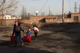 2010年11月29日,包头市郊包钢尾矿坝附近的新光一村。打工者张秀丽因无法忍受污染,带着两个小孩准备搬家到市区。
