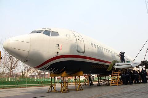 维修人员正在对波音737-300飞机进行机翼组装作业. 闻舞/cfp