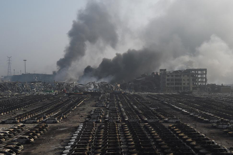 Smoke billows behind rows of burnt out cars at the site of a series of explosions in Tianjin