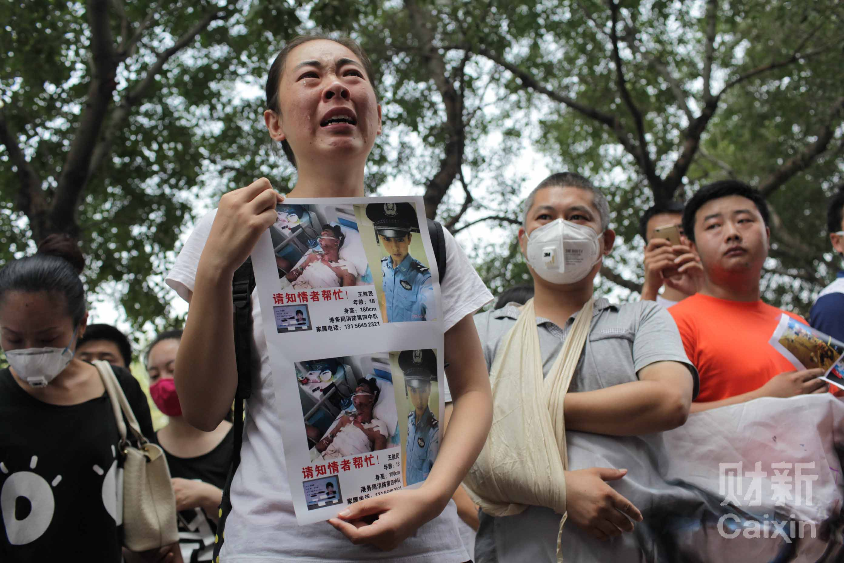 IMG_0194 港务局消防第四中队王胜民的家人举着照片在美华大酒店门前哭诉。副本-10