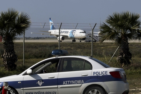 Police stand guard at Larnaca Airport near a hijacked Egyptair Airbus A320