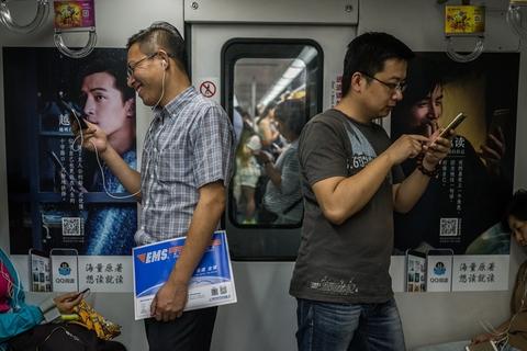 2016年5月30日,地铁车厢内玩手机的人.在地铁里,随处可见低头族.