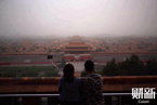 北京遭遇今春最严重沙尘 昏黄一片行人掩面