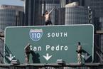 美国男子抗议污染 爬上高速公路指示牌做后空翻