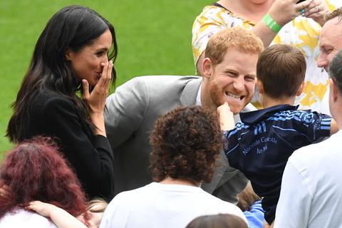 2018年7月11日,爱尔兰都柏林,哈里王子和梅根王妃出访爱尔兰,在克罗克体育场参观访问。哈里王子的大胡子遭顽皮的小孩伸手抚摸,一旁的梅根也被逗笑。图/视觉中国