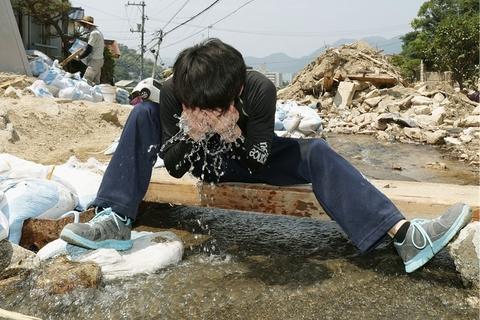 当地时间2018年7月18日,日本广岛县吴市,暴雨灾区志愿者洗脸。暴雨过后,日本多地又迎来高温天气。由于罕见高温的袭击,军队和志愿者们在灾区的救援和恢复工作也遭遇了阻碍。据英国《独立报》报道,上周末以来,这股强烈的热浪横扫日本,已造成14人死亡,上千人在医院接受中暑治疗。图/视觉中国