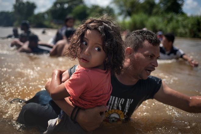 中美洲移民大军持续北上赴美 手拉手组人链渡河