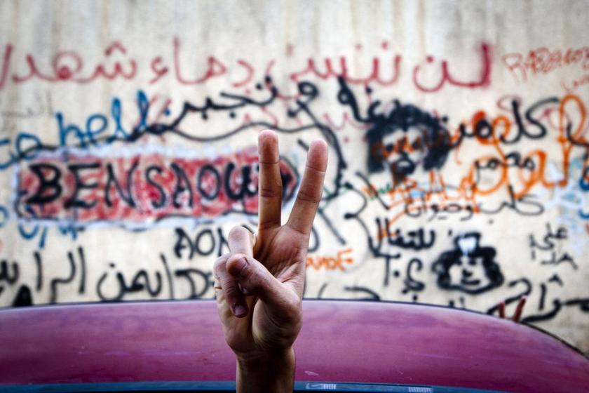 """10月18日,利比亚班加西,一人在讽刺卡扎菲的涂鸦墙前摆出胜利手势。10月20日,利比亚""""全国过渡委员会""""执行委员会主席贾布里勒证实,卡扎菲当天在苏尔特身亡。 CFP_财新每周图片(2011.10.15-10.21)"""