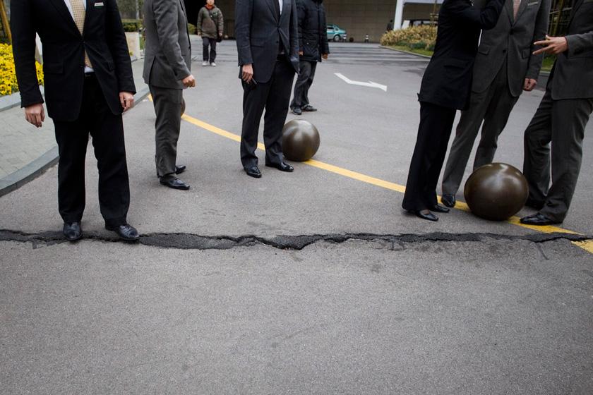 2月16日,上海陆家嘴环球金融中心的工作人员在检查地面裂缝情况,裂痕与在建的上海中心有一街之隔。贾代腾飞/CFP _财新每周图片(2012.2.11-2.17)