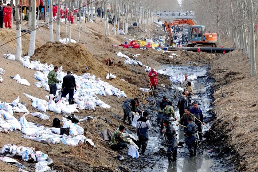 3月28日,现场工人在大型机械的配合下全力清理油污。 东方IC_北京通州输油管道破裂污染河道