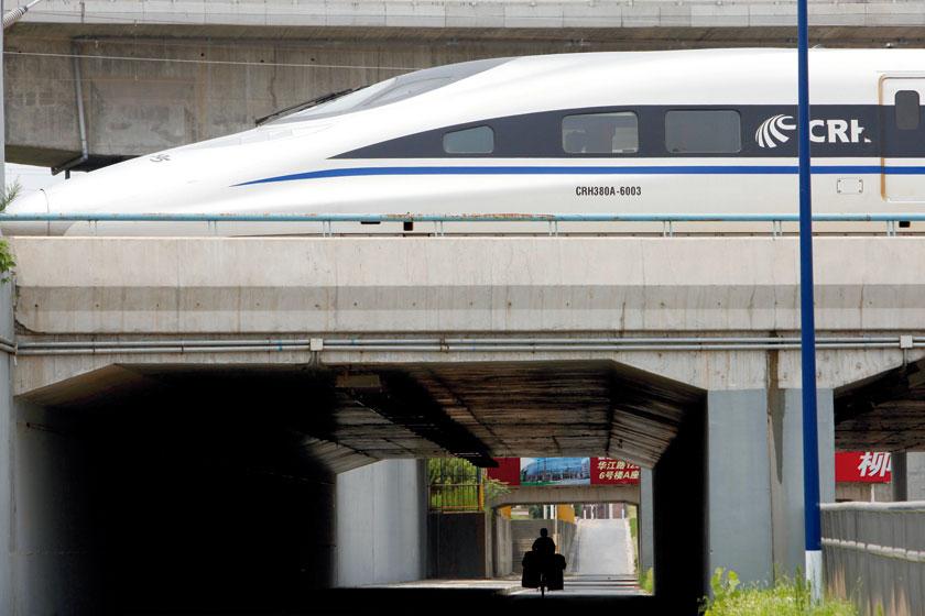 2011年7月27日,上海郊区,一名男子从高铁列车检修中心隧道下骑车经过。_高铁国产化幻觉