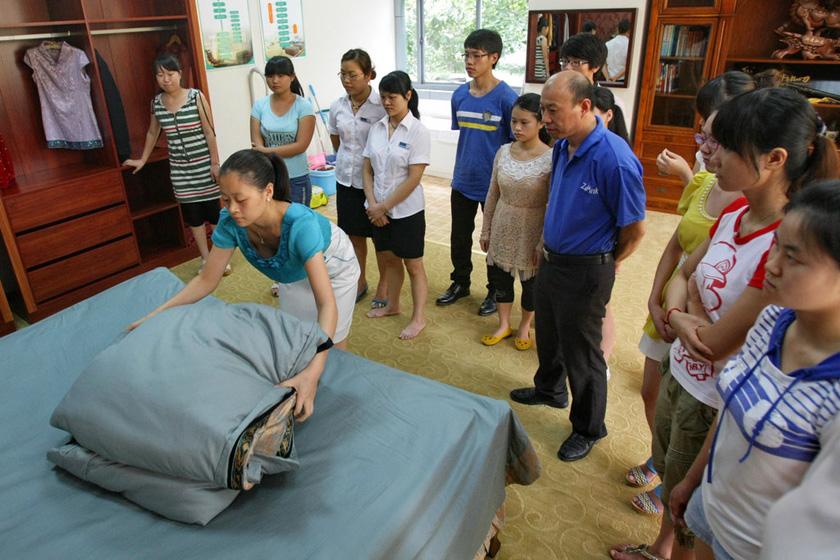 7月11日,重庆,铺床叠被,看似简单,细节却容易被忽略。  东方IC_重庆11名女大学生应聘当保姆