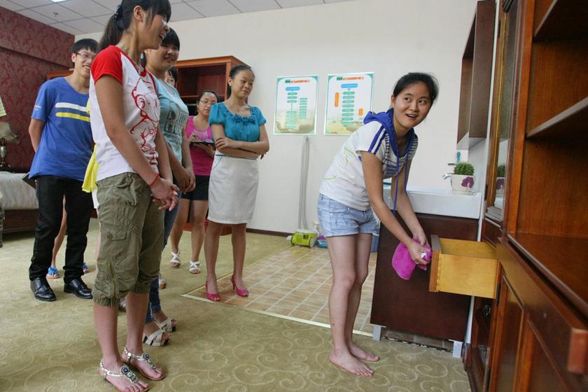 重庆,学生擦完抽屉,不自信的问老师成绩,得到的答复是不合格。  东方IC_重庆11名女大学生应聘当保姆