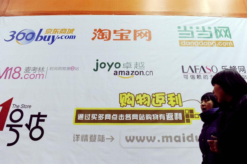 2012年1月3日,河南省郑州市,行人走过一面写有很多电商企业名称的广告墙。_决战电商