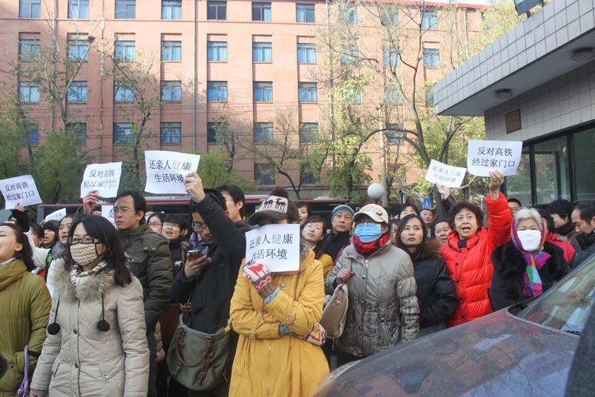 11月29日,京包线沿线小区的数百居民举着标语聚集在北京市规划委。   何林璘/财新实习记者_北京数千市民联名质疑京沈高铁环评
