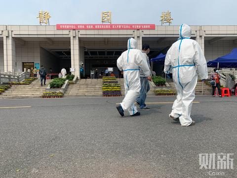 2020年3月26日下午,武汉汉口殡仪馆,身着防护服的工作人员走过。当天上午,排队亲属从汉口殡仪馆静雅厅的大门口一直蜿蜒延伸至东侧乾和厅的门前,有近200米长。 图/财新记者 丁刚