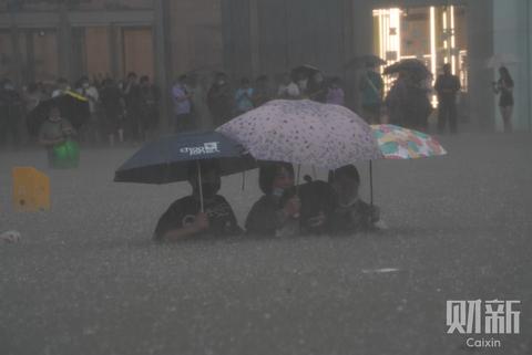 今天下午,河南郑州,东风路与花园路交叉口附近,民众冒雨出行,路面积水没过胸口。7月16日至20日,河南郑州连降暴雨,多条河流水位上升较快,多座水库超汛限,据气象部门预报,今明两天,郑州市仍以大到暴雨天气为主,防汛形势进一步复杂严峻。图/财新记者陈亮