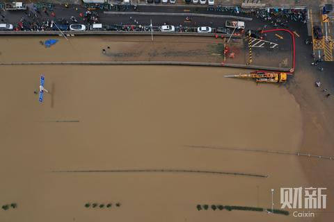 7月21日11时至12时,记者航拍降雨暂停的郑州部分路段。20日,郑州市受强降雨影响,单日降雨量突破历史极值,单小时降雨量超过日历史极值,降雨造成郑州市区严重内涝,市内交通中断,多处小区停水停电。截至7月21日早7时,全市受灾人口3.6万人,紧急转移近20万人。图/财新记者陈亮